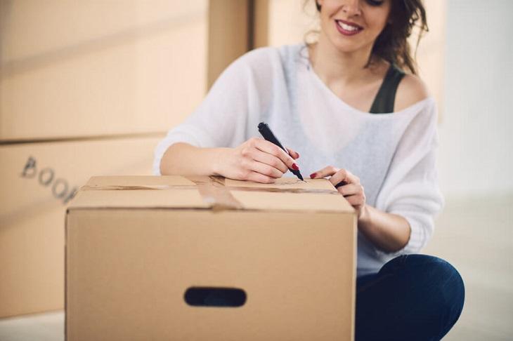טיפים למעבר דירה: אישה כותבת על קופסת קרטון