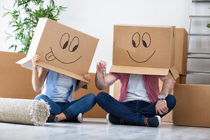 טיפים למעבר דירה: זוג חובש קופסאות קרטון עם ציון סמיילי על הראש