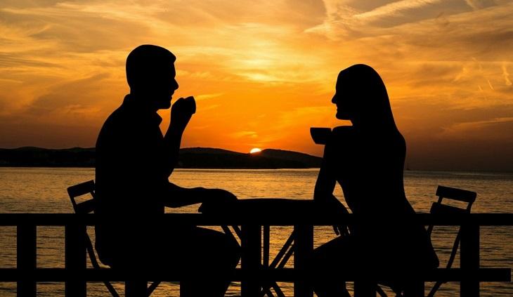 סימנים מפתיעים למשבר אמצע החיים: זוג שותה קפה על רקע שקיעה
