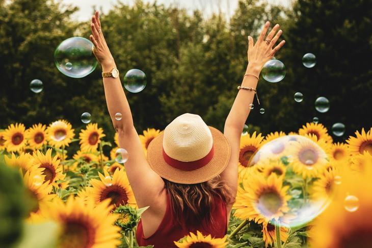 א'-ב' של האושר: אישה מרימה ידיים למעלה בשדה חמניות וסביבה בועות סבון