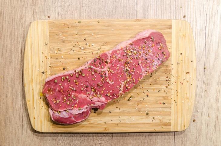 מגמות בריאותיות משנות העשר: חתיכת בשר מתובלת, מונחת על קרש חיתוך
