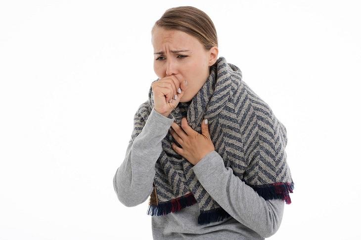 נקודות לחיצה לטיפול בכאבי גרון: אישה משתעלת