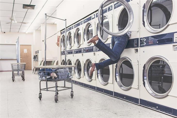 טיפים לניקוי יבש: אישה עם חצי גוף בתוך מכונת כביסה במכבסה