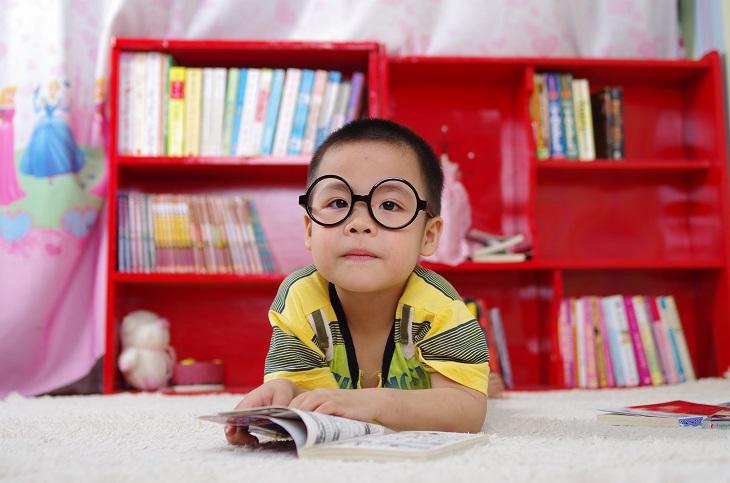 טיפים של מארי קונדו לסידור חדרי ילדים: ילד קורא ספר בחדרו על רקע ספרייתו