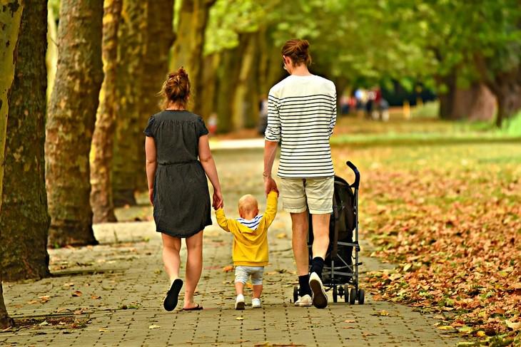 טריקים של הורים מאושרים: זוג הורים הולך עם ילדם יד ביד