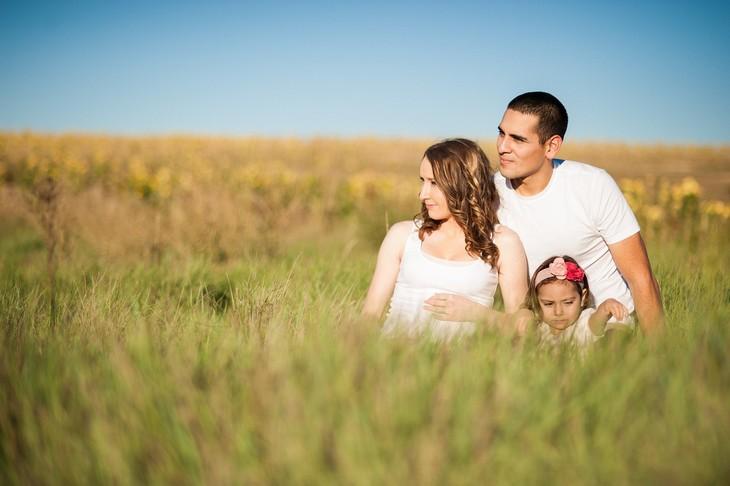 טריקים של הורים מאושרים: זוג הורים וילדתם יושבים בשדה