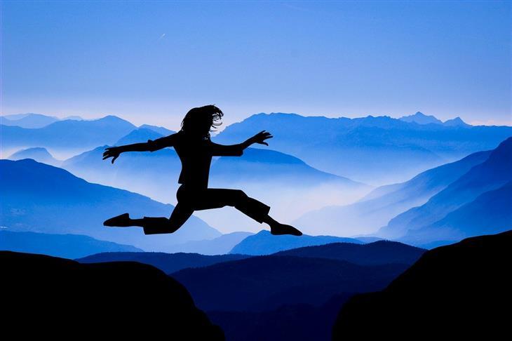 אתגרים שיחזקו אתכם מדי יום: צללית של אישה קופצת בין שתי גבעות