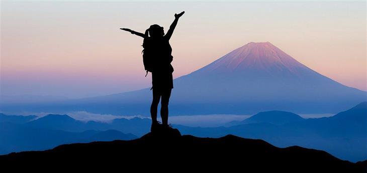 אתגרים שיחזקו אתכם מדי יום: צללית של אישה עומדת על הר ומרימה ידיים מעלה