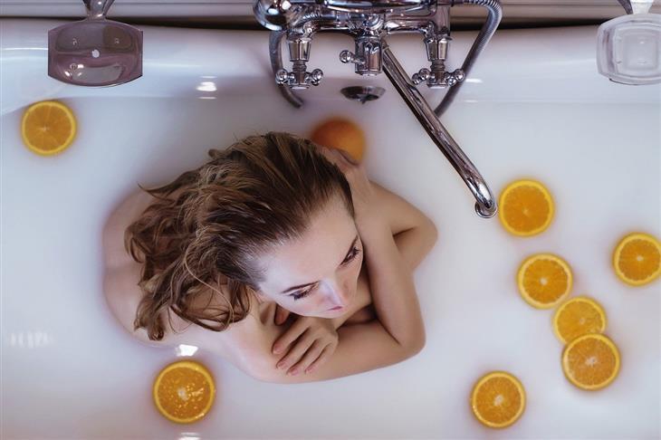 דברים שאפשר להוסיף לאמבטיה: אישה באמבטיית חלב וחתיכות תפוז