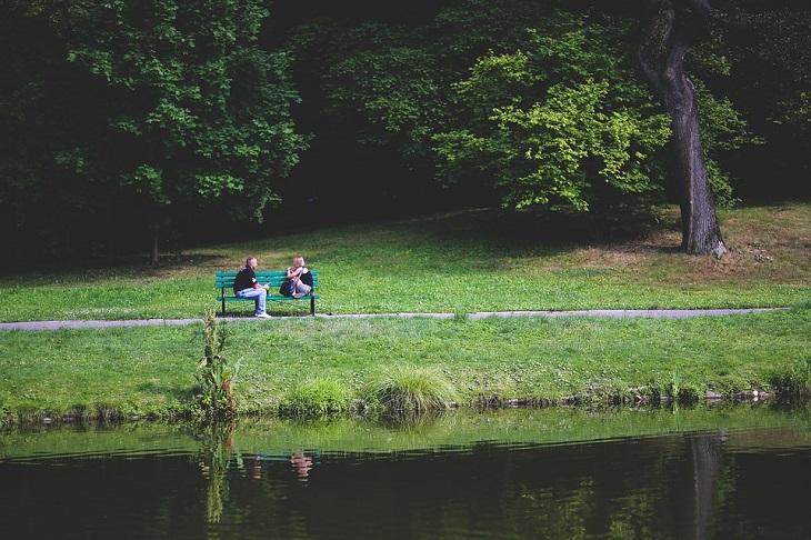 שלבים לבנייה מחדש של אמון: גבר ואישה יושבים על ספסל בקרבת אגם ומדברים ביניהם