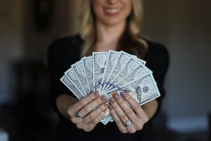 אנשים מעוכבי התפתחות רגשית: אישה מחזיקה מול המצלמה שטרות דולר פרוסים