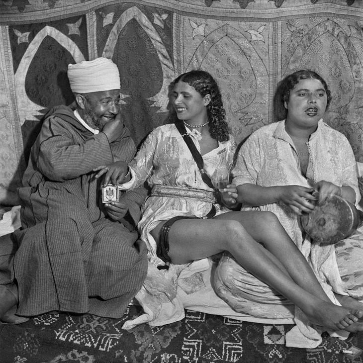 תמונות היסטוריות: רקדנית יושבת בין נגנית למכובד מרוקאי בעיר לראצ'ה, מרוקו, 1942.