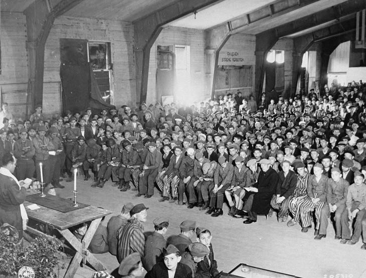 תמונות היסטוריות: ניצולי שואה יהודים ממחנה הריכוז בוכנוואלד יחד עם חיילים יהודים מצבא ארצות הברית שעזרו לשחרר את המחנה ביום הראשון של חג השבועות, עורכים סדר שבועות בהובלת הרב הרשל שכטר, 18 במאי, 1945.