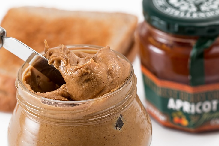 יתרונות סוגי חמאה: סכין למריחה בתוך צנצנת חמאת בוטנים