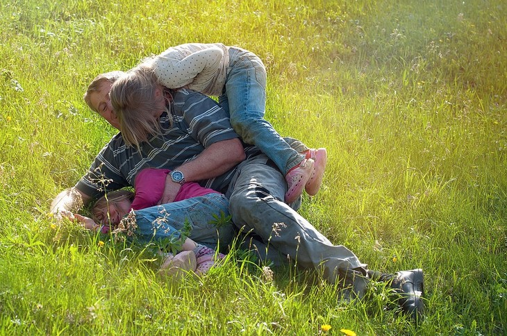מחקר אבות מאושרים: אבא משחק עם שתי בנותיו בדשא