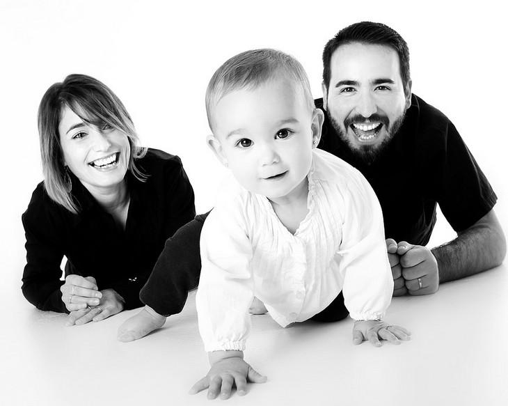 מחקר אבות מאושרים: שני הורים שוכבים מחויכים ולפניהם זוחל תינוק
