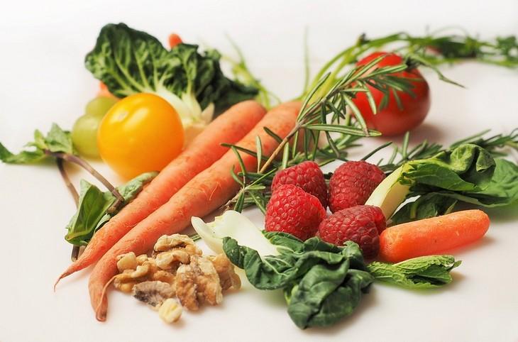 הדיאטה שמונעת אלצהיימר: גזרים, פירות יער, תות, פלפל, עלי כרוב, עלי תרד ואגוזי מלך מונחים על שולחן