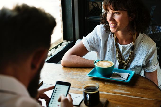 בחן את עצמך: אישה יושבת מול גבר בבית קפה והוא משתמש בסמארטפון