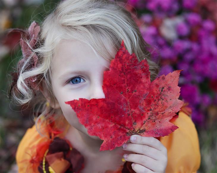 עצות מפסיכולוגית לגידול ילדים: ילדה מחזיקה עלה מול פניה