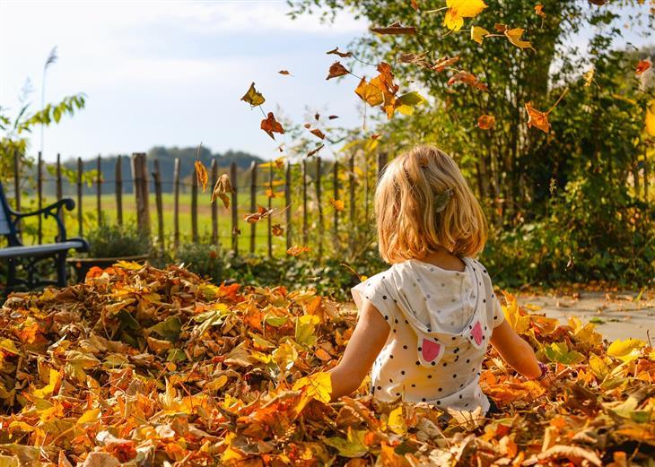 עצות מפסיכולוגית לגידול ילדים: ילדה יושבת בתוך ערימת עלים