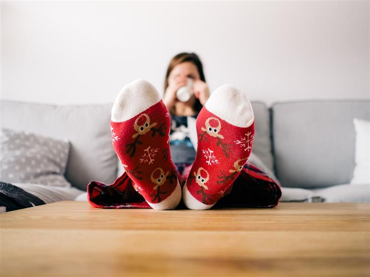 דברים שתתחרטו עליהם בעתיד: אישה יושבת על ספה עם רגליים על השולחן ושותה משקה חם