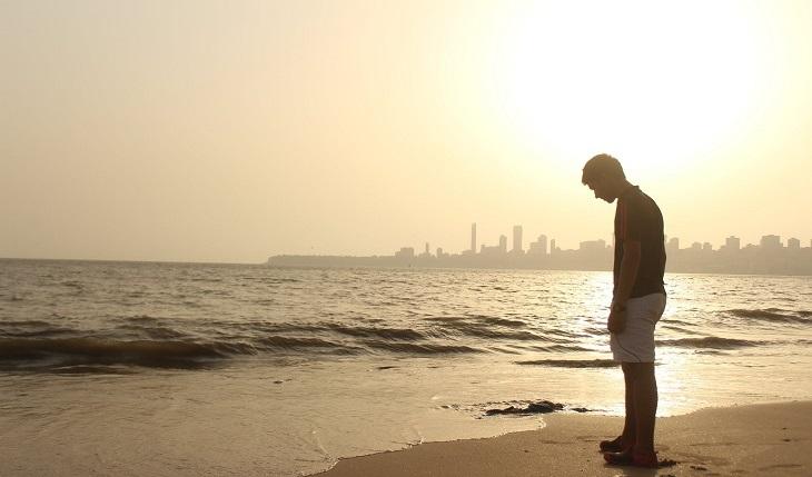 סימנים שצריך לעשות שינוי בחיים: אדם מרכין ראש על חוף הים