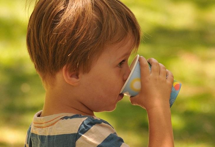 טיפים למניעת הרטבת לילה: ילד שותה מכוס על רקע שמש הבוקר