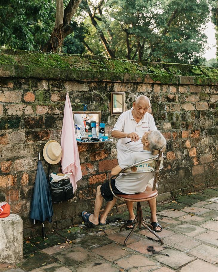 צפון ויאטנם: ספר מגלח גבר מבוגר לצד קיר מקדש
