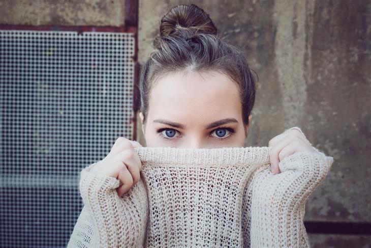 איך להמריץ את מערכת הלימפה: אישה מותחת סוודר מול פניה
