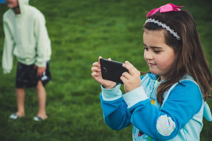 שיטות לעזור לילד להתחבר עם אחרים: ילדה משחקת בנייד לבד
