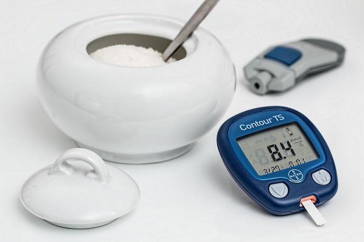 תה פטרוזיליה: קערת סוכר לצד מכשירים למדידת סוכרת