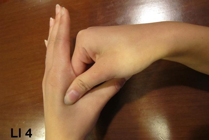 נקודת לחיצה לטיפול במיגרנות: אישה לוחצת עם האצבעות על נקודת LI-4