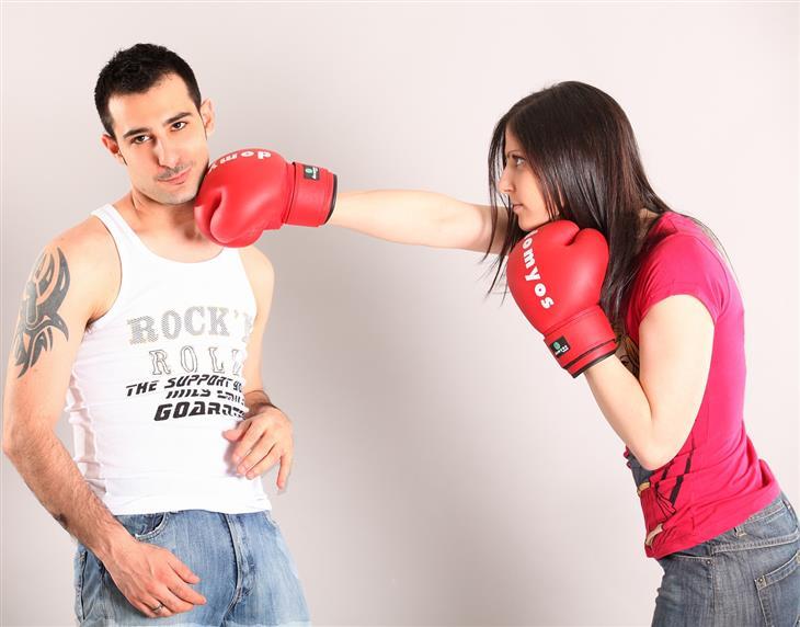דרכים להתמודדות כשבני הזוג לא מסתדרים עם ההורים: אישה עם כפפות איגרוף נותנת אגרוף לגבר שלא נרתע