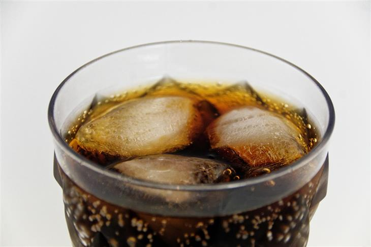 הקשר בין שתיית משקאות קלים למחלות לב: כוס קולה עם קרח