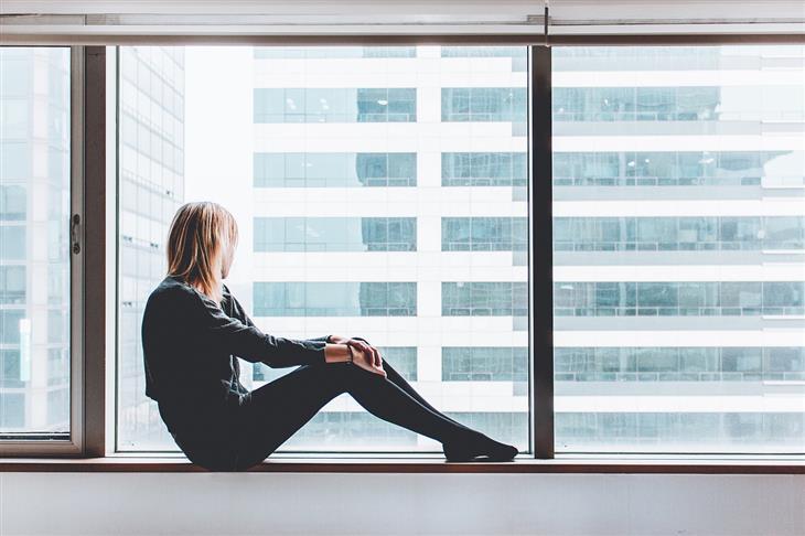 דברים שצריך להפסיק לעשות כשהחיים לא הולכים כמתוכנן: אישה יושבת על אדן חלון ומסתכלת החוצה