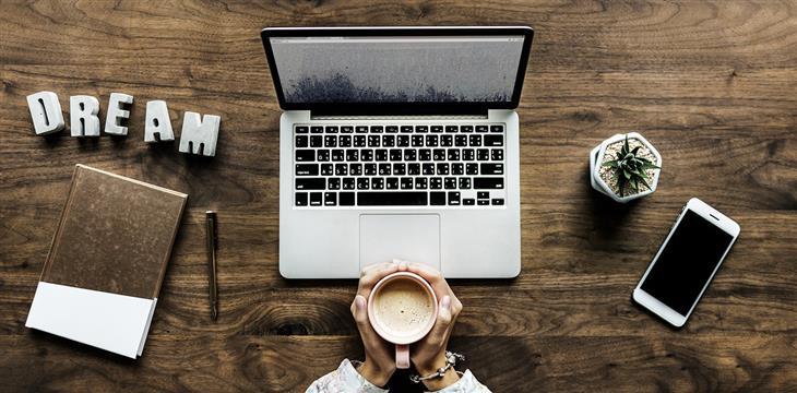 דברים שצריך להפסיק לעשות כשהחיים לא הולכים כמתוכנן: ידיים מחזיקות כוס קפה מול מחשב נייד