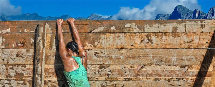 דברים שצריך להפסיק לעשות כשהחיים לא הולכים כמתוכנן: אישה מנסה לטפס על קיר