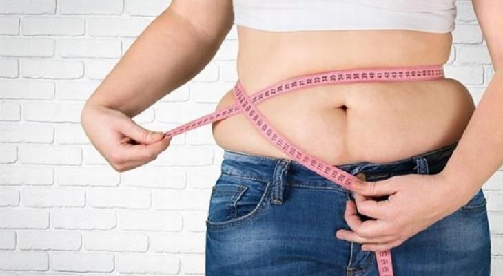שומן בטן: אישה כורכת סביב הבטן שלה סרט מדידה צמוד