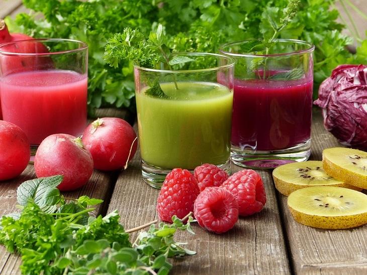 רפואה פונקציונאלית: 2 כוסות מיץ ופירות מונחים על שולחן עץ
