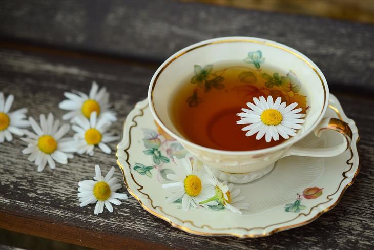 יתרונות בריאותיים של קמומיל: כוס תה עם פרח קמומיל עליה