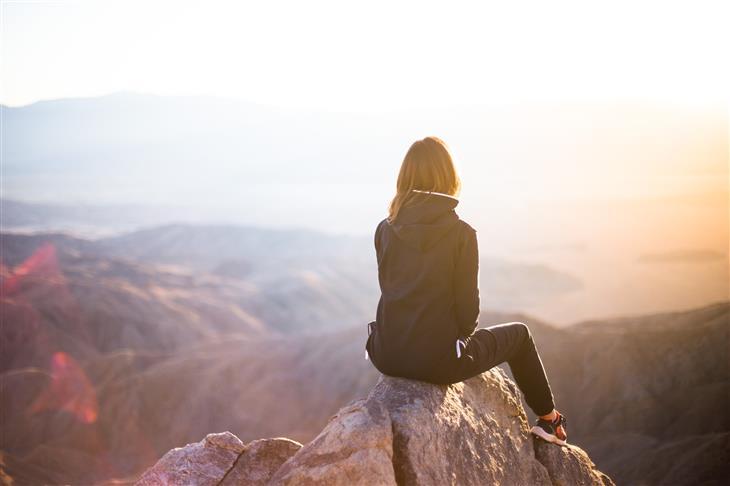 עצות לחיים טובים: אישה יושבת על צוק ומסתכלת על הנוף שלפניה