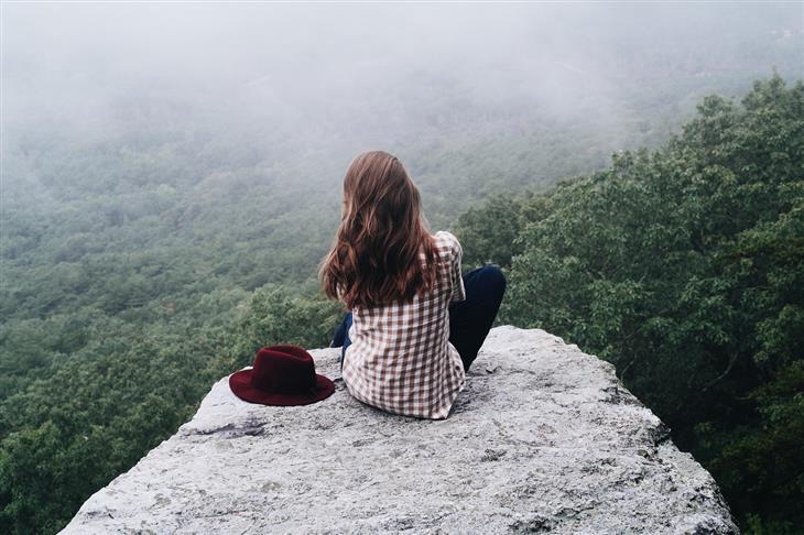 עצות לחיים טובים: אישה יושבת על צוק ומסתכלת על הנוף שמולה