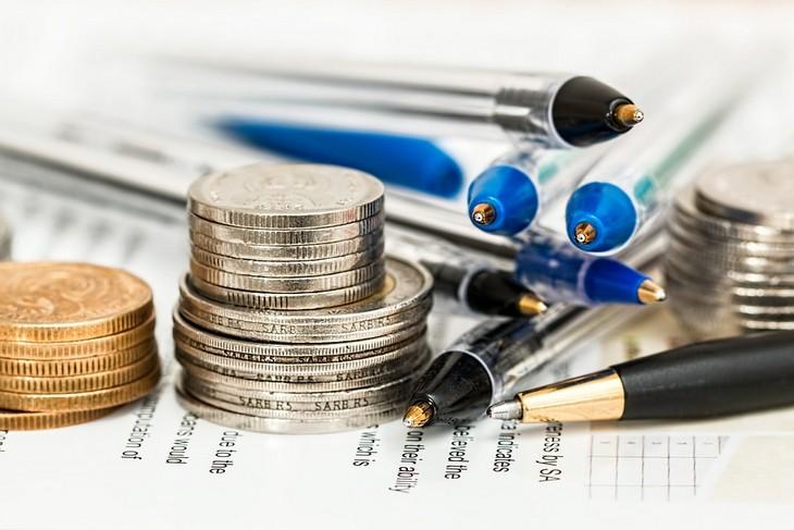 מה צריך לדעת לפני טיפול זוגי: דף ועליו מונחים בערמה עטים ומגדלי מטבעות