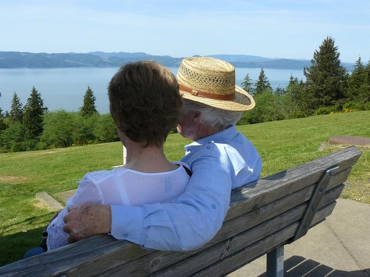מה צריך לדעת לפני טיפול זוגי: זוג מבוגרים יושבים מחובקים על ספסל