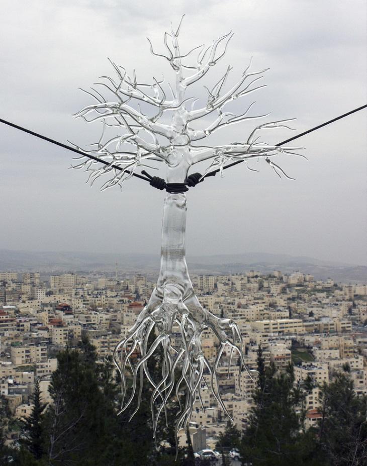 יצירות זכוכית של סימון קרסטני: עץ זכוכית קשור מעל נוף עירוני