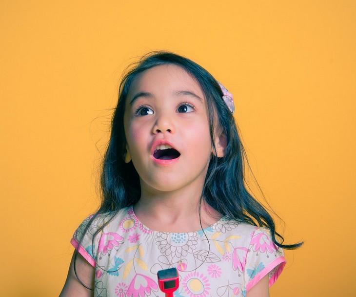 סימנים שילדים משקרים: ילדה מסתכלת ופוערת את פיה
