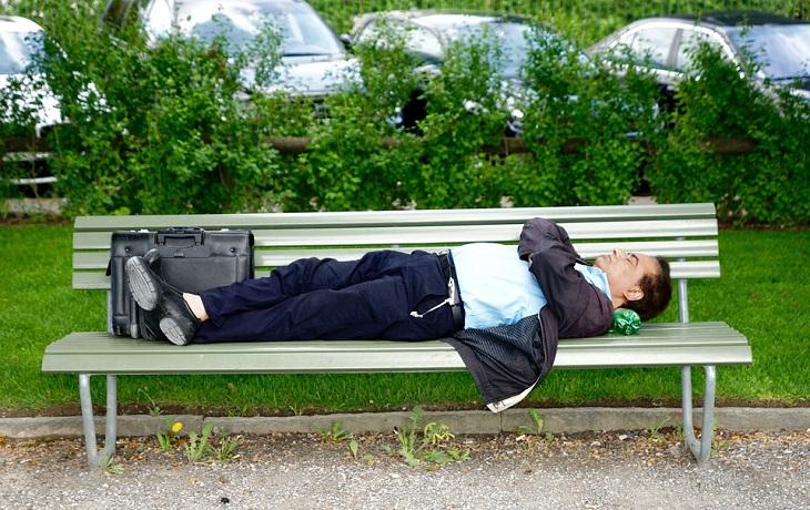 בעיות בריאותיות שמשפיעות על השינה: גבר בחליפת עסקים ישן על ספסל ציבורי