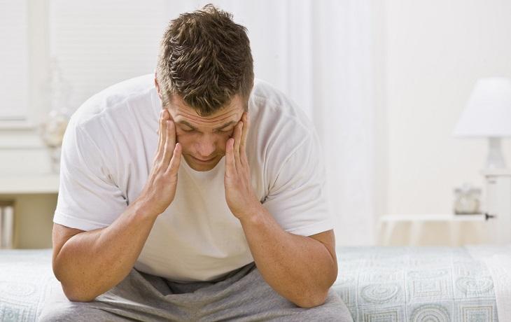 בעיות בריאותיות שמשפיעות על השינה: גבר עייף עם כאב ראש יושב על מיטה