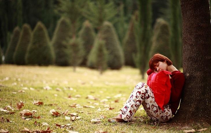 בעיות בריאותיות שמשפיעות על השינה: אישה עייפה ישנה ליד עץ