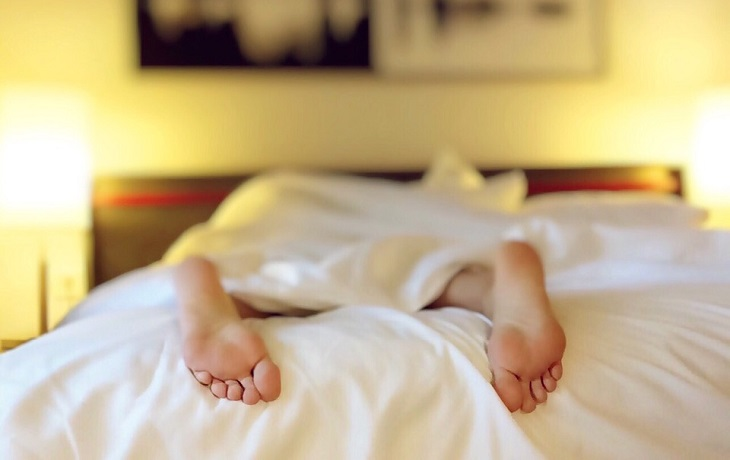 בעיות בריאותיות שמשפיעות על השינה: רגליים של אדם ישן מציצות מקצה מיטה